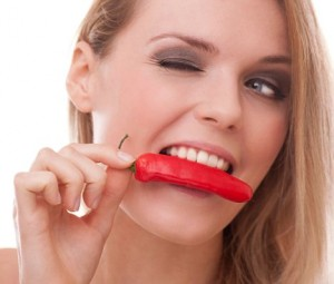 woman biting into a hot red chilli / photo from http://www.dailymail.co.uk
